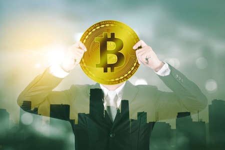 Double exposure of businessman covering his face with bitcoin symbol while standing with modern city background Zdjęcie Seryjne
