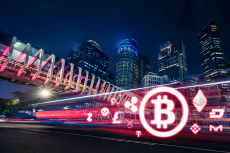 Image of Bitcoin symbol speeding on the road at night time with skyscrapers in Jakarta city Zdjęcie Seryjne - 164585170
