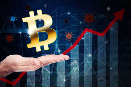 Hand showing bitcoin symbol with growth financial chart and covid-19 or bitcoin representing the stock market success during Coronavirus pandemic