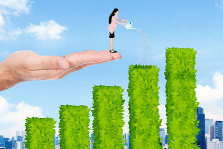 Caucasian businesswoman watering plant shaped growth graph while standing on the helping hand with blue sky background Zdjęcie Seryjne