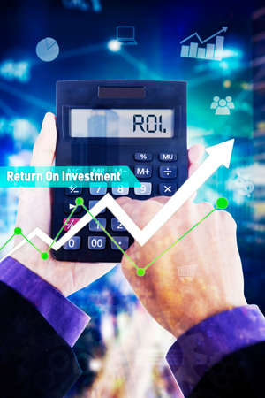 Close up of businessman hands using a calculator with ROI word and growth business chart in virtual screen background Zdjęcie Seryjne - 164582488
