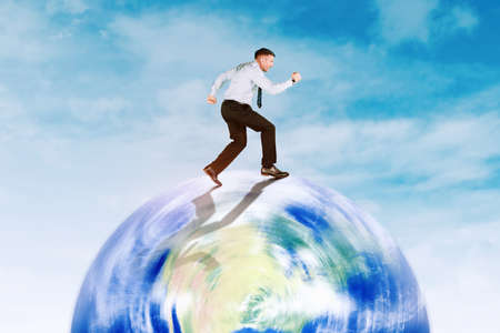 Side view of caucasian businessman looks hurry while running fast around the earth with blue sky background