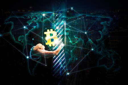 Double exposure of businessman hand showing bitcoin symbol with connection network and modern city background