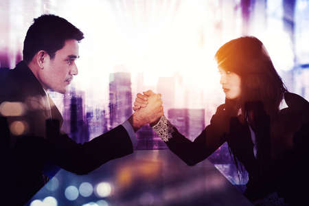 Double exposure of businessman and businesswoman having conflict while doing arm wrestling in the office with cityscape background