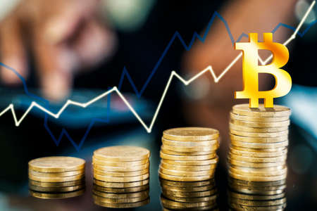 Close up of bitcoin symbol above gold coins shaping growth chart on the table Zdjęcie Seryjne