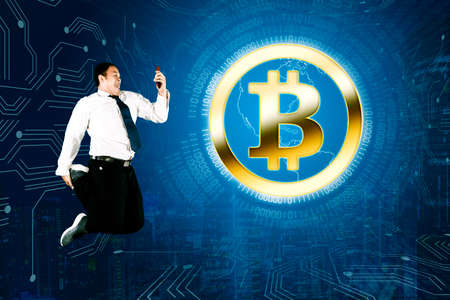 Double exposure of businessman using a cellphone while jumping with bitcoin symbol in cyberspace background