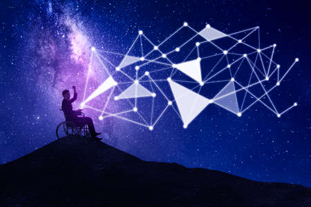 Disabled businessman using a smartphone while sitting on the hill with connection network symbol and milky way in the sky Zdjęcie Seryjne