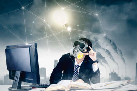 Businessman wearing gas mask while looking at a bright bulb with network connection in polluted city background