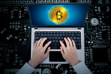 Top view of businessman typing on computer laptop with bitcoin symbol in circuit board background Zdjęcie Seryjne