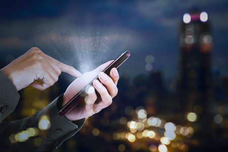 Close up of businessman hands touching a bright phone screen while standing with blurred night city background Zdjęcie Seryjne