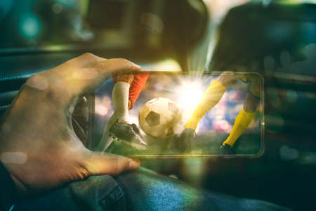 Close up of young man hand using a mobile phone to watching football match while sitting inside a car