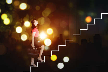 Side view of female manager carrying a suitcase while climbing stairs with blurred sparkling lights background Zdjęcie Seryjne