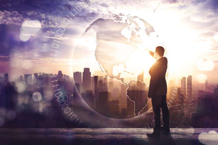 Back view of businessman touching a globe button on virtual screen while standing on the office rooftop with cityscape at sunrise time Zdjęcie Seryjne - 164460287