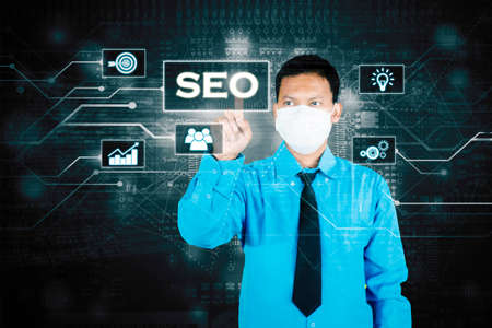 Picture of businessman wearing face mask while touching SEO button on the virtual screen