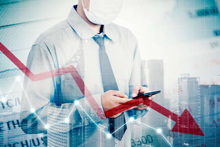 Double exposure of businessman wearing face mask while using a cellphone and standing near declining arrow with modern city background Zdjęcie Seryjne