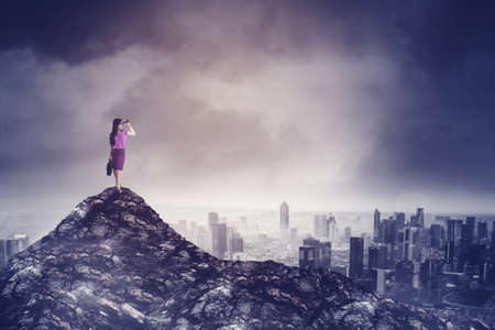 Portrait of female manager using binoculars to looking at the stormy in a city while standing on the peak of mountain