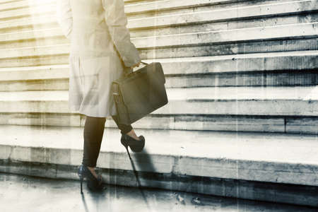Close up of businesswoman feet wearing high heels and climbing stairs while carrying a suitcase