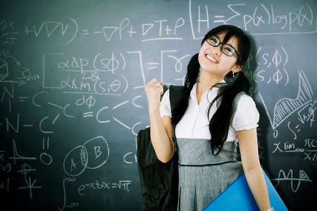 Female student expressing happy by lifting hand while standing with math formulas on chalkboard. Shot in the classroom