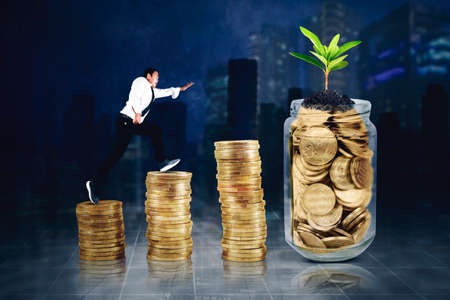 Side view of businessman running above stacks of gold coins shaped growth chart toward a jar full of gold coins with night city background Zdjęcie Seryjne