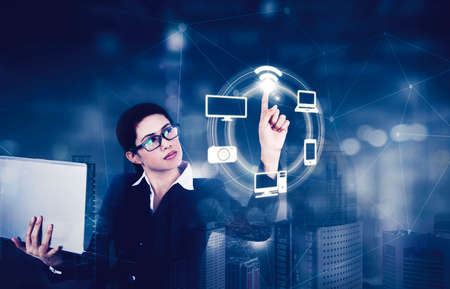 Double exposure of businesswoman holding a laptop while touching wifi symbol on the virtual screen