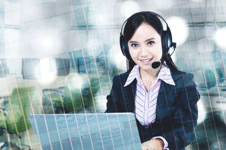Double exposure of female call center operator smiling at the camera while working with headphone and computer
