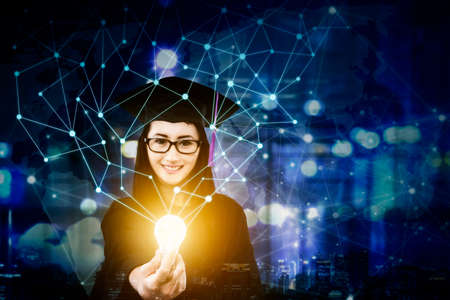 Female college student wearing graduation gown while holding a bright bulb with connection network in night city background