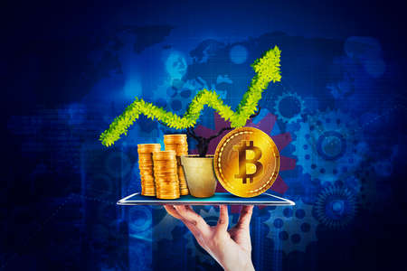 Close up of hand holding a digital tablet with a stack of gold coins, upward arrow and bitcoin in virtual screen background Zdjęcie Seryjne