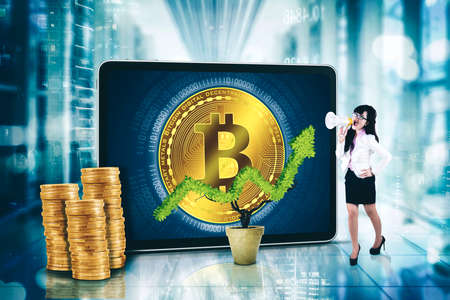 Businesswoman using a megaphone while standing with bitcoin symbol on computer screen and a plant shaping upward arrow Zdjęcie Seryjne