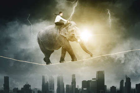 Side view of Caucasian businessman riding an elephant while walking on a rope above city with lightning storm background