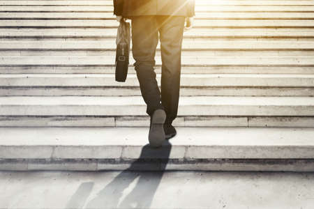 Close up of businessman feet walking on the stairs while carrying a suitcase