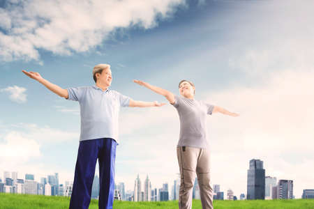 Low angle view of happy old couple wearing sportswear while doing gymnastics exercise together at park with modern city background