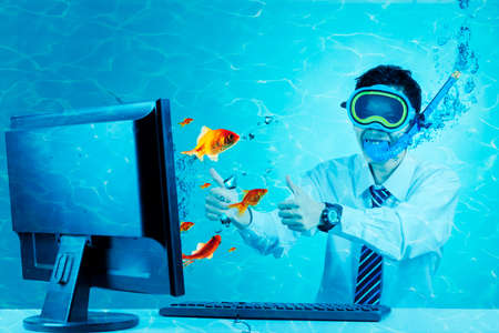 Funny businessman showing thumbs up on the computer monitor with golden fishes while wearing snorkeling equipment and diving at underwater