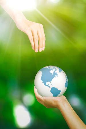 God hand saving an earth globe from human hands on blurred green background Zdjęcie Seryjne