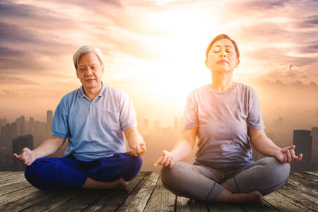 Elderly couple wearing sportswear while practicing yoga and sitting with cityscape at sunset time. Shot at outdoors