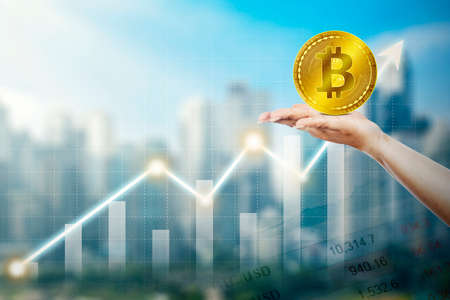 Close up of unknown hand holding bitcoin symbol with growth financial chart and cityscape background