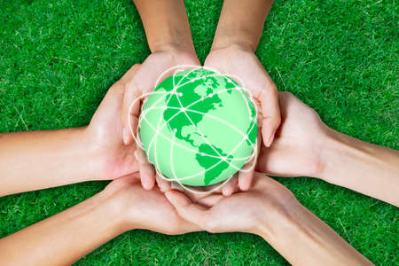 Close up of three people hands holding an earth planet with connection network in green grass background