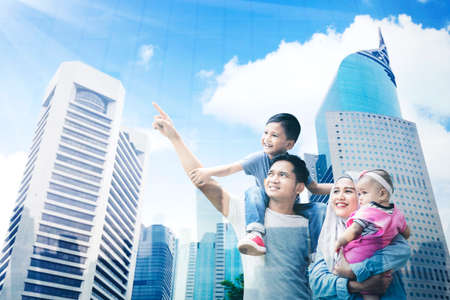 Low angle view of a happy Muslim family enjoying leisure time together while looking at modern city view