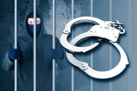 Close up of silver handcuffs with background of arrested hacker in prison Zdjęcie Seryjne