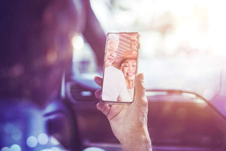 Back view of old man doing video call with his friends on a mobile phone while sitting in the car with sunlight background