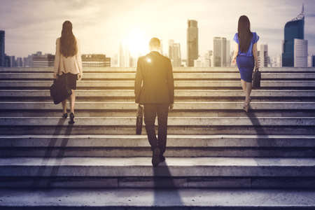 Rear view of three business people carrying suitcase while climbing stairs toward bright modern city background