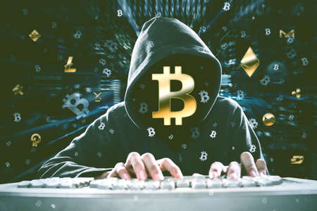 Hooded hacker using a computer to hacking information with bitcoin symbol in code binary background