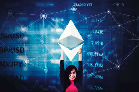 Young businesswoman holding ethereum symbol while standing with trade stock exchange background