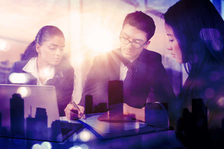 Group of three business people doing business meeting in the office with double exposure of modern city background