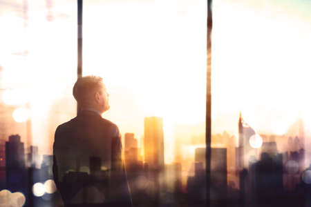Double exposure of pensive male manager looking at cityscape while standing near the window in the office at dusk time