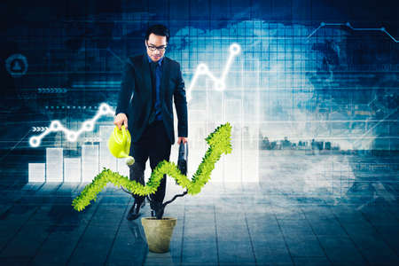Businessman watering a plant shaped upward arrow while standing with double exposure of cityscape and virtual screen background Zdjęcie Seryjne