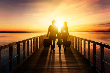 Silhouette of little girl holding hands her parents while walking together on the wooden jetty with dramatic sky background
