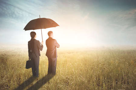 Back view of businesswoman protecting her boss by using an umbrella while standing on the meadow. Shot at sunrise time