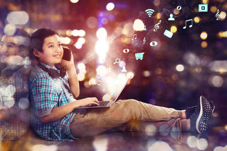 Double exposure of preteen schoolboy make a call phone while using a laptop with notification social media icons in blurred sparkling light background Zdjęcie Seryjne