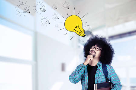 Male Afro student thinking an idea while looking at a bright bulb over his head and standing in the classroom