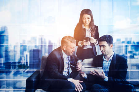 Double exposure of three diversity business people using a tablet while discussing together with modern city background Zdjęcie Seryjne